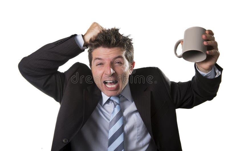 Hombre de negocios joven del adicto en traje y lazo que sostiene la taza de café vacía ansiosa fotos de archivo libres de regalías