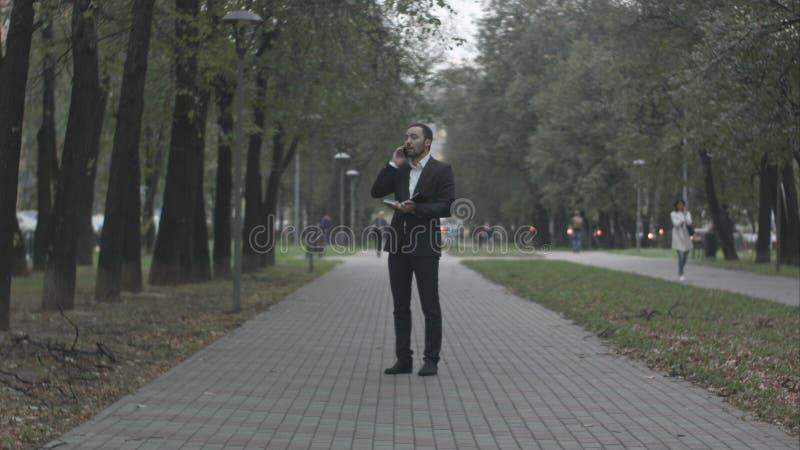 Hombre de negocios joven en callejón del parque que habla por el teléfono y que escribe en el diario, trabajando con las notas en imágenes de archivo libres de regalías