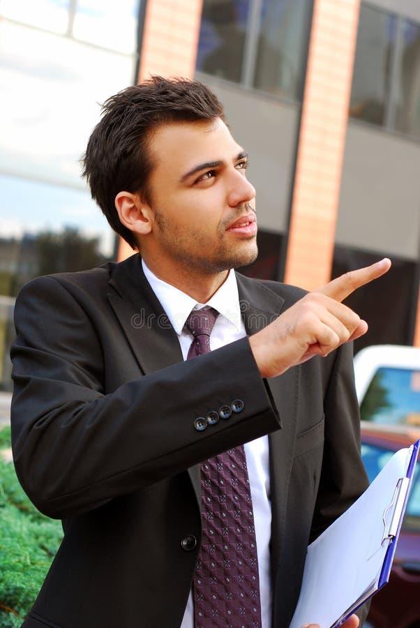 Hombre de negocios joven en el frente de la oficina foto de archivo libre de regalías