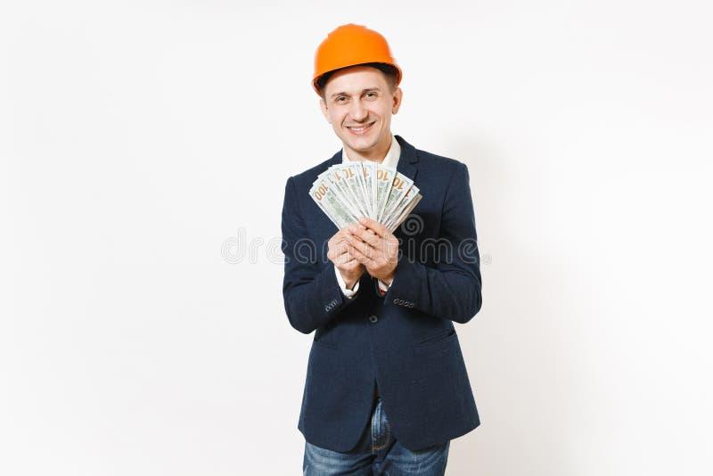 Hombre de negocios joven en el traje oscuro, paquete protector de la tenencia del casco de la construcción de dólares, dinero del fotos de archivo