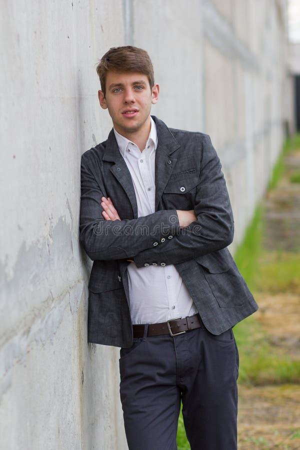 Hombre de negocios joven en el traje que se inclina en la pared imágenes de archivo libres de regalías