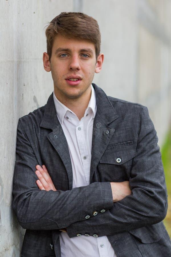 Hombre de negocios joven en el traje que se inclina en la pared imagen de archivo