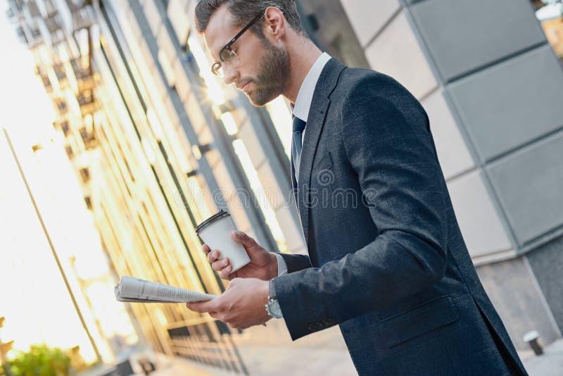 Hombre de negocios joven en el traje y los vidrios que sostienen una taza de papel y que leen el periódico de negocios en sus man fotografía de archivo