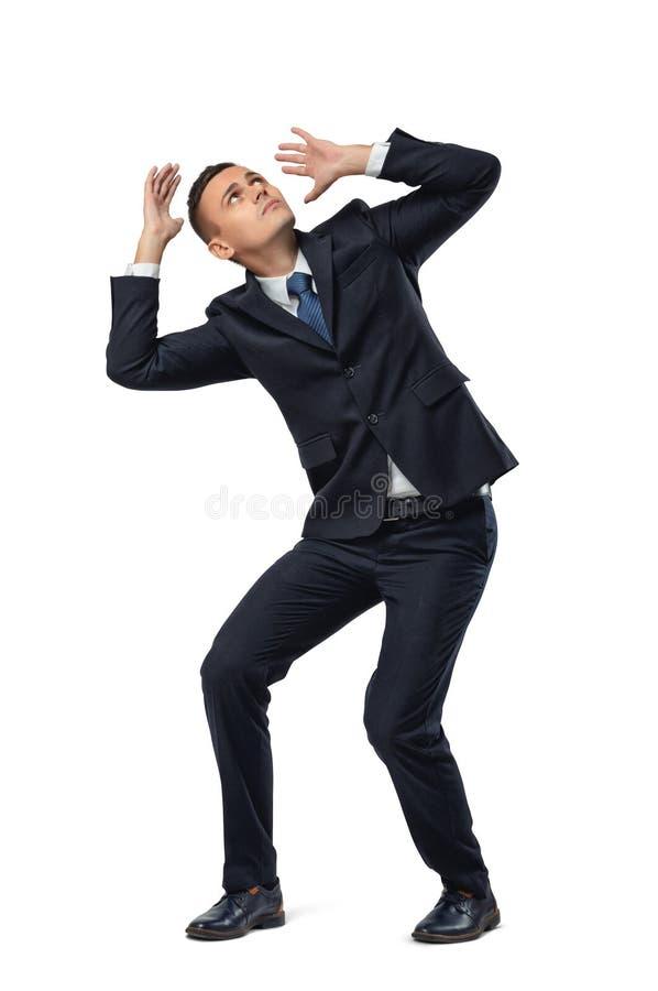 Hombre de negocios joven en la actitud defensiva asustada algo aislado en el fondo blanco fotos de archivo