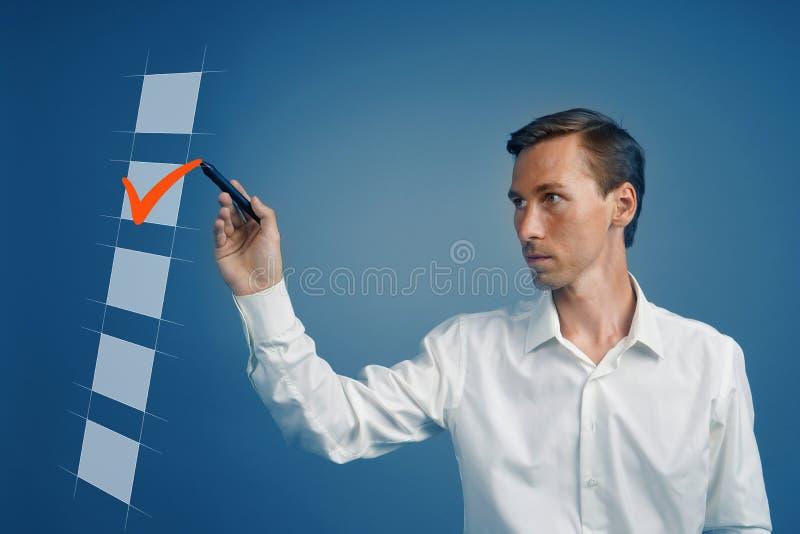 Hombre de negocios joven en la camisa blanca que comprueba la caja de la lista de control Fondo para una tarjeta de la invitación fotografía de archivo