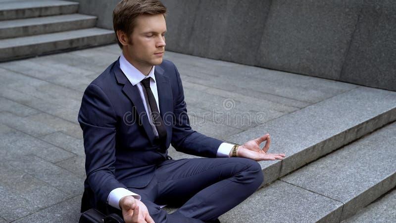 Hombre de negocios joven en la posición de loto que calma abajo después de la reunión importante, tensión imagen de archivo