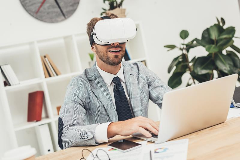 hombre de negocios joven en las auriculares del vr que trabajan con el ordenador portátil imágenes de archivo libres de regalías