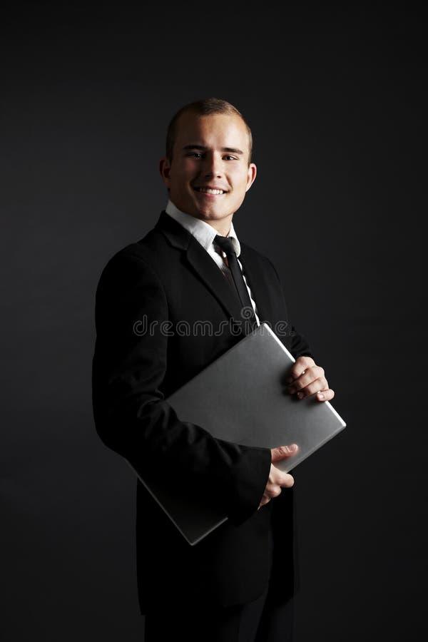 Hombre de negocios joven en negro con la computadora portátil fotos de archivo libres de regalías