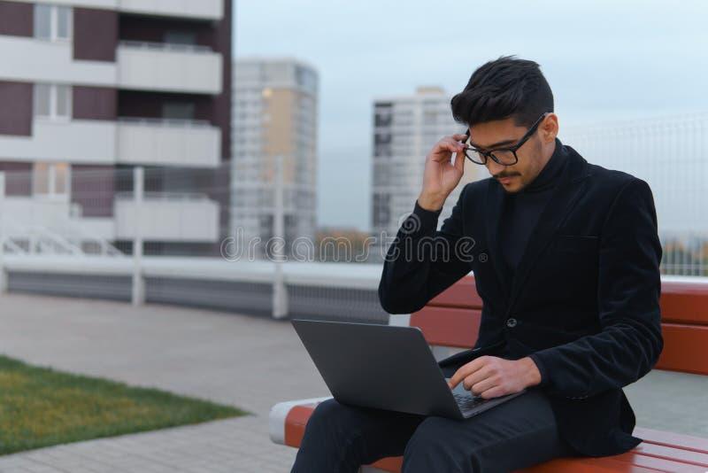 Hombre de negocios joven en ordenador de trabajo negro del ablet del tiempo largo del traje y al aire libre cansado imagen de archivo libre de regalías