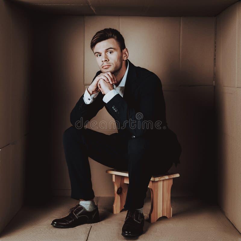 Hombre de negocios joven en traje negro en caja de cartón imágenes de archivo libres de regalías