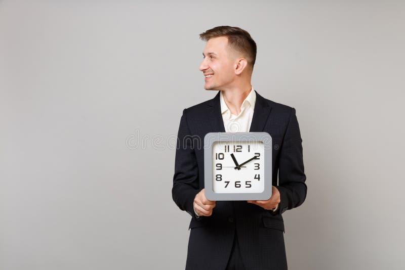 Hombre de negocios joven en traje negro clásico y la camisa blanca que miran a un lado, sosteniendo el reloj cuadrado aislado en  fotografía de archivo