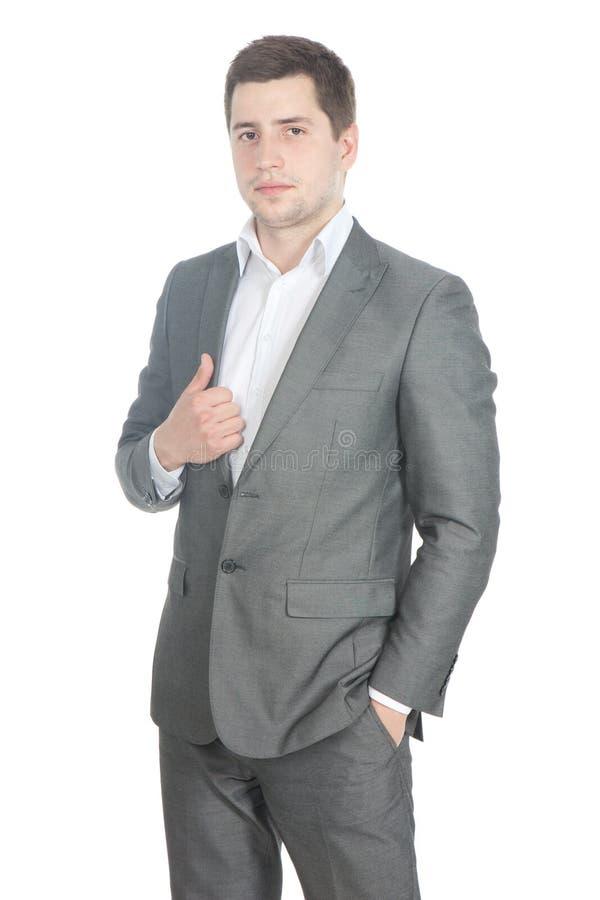 Hombre de negocios joven en un juego gris sobre blanco fotografía de archivo