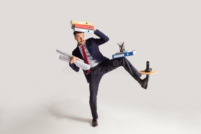 Hombre de negocios joven en un traje que hace juegos malabares con los materiales de oficina en su oficina, aislada en el fondo b fotografía de archivo libre de regalías