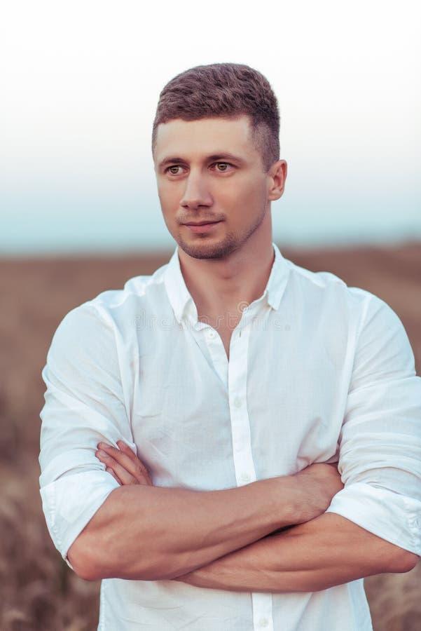 Hombre de negocios joven en una camisa blanca Se coloca en el campo de trigo, un día de verano caliente Emocionalmente mirando en fotografía de archivo