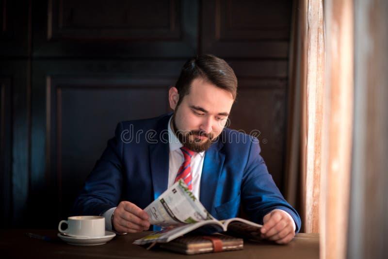 Hombre de negocios joven en una revista de la lectura del café fotografía de archivo libre de regalías