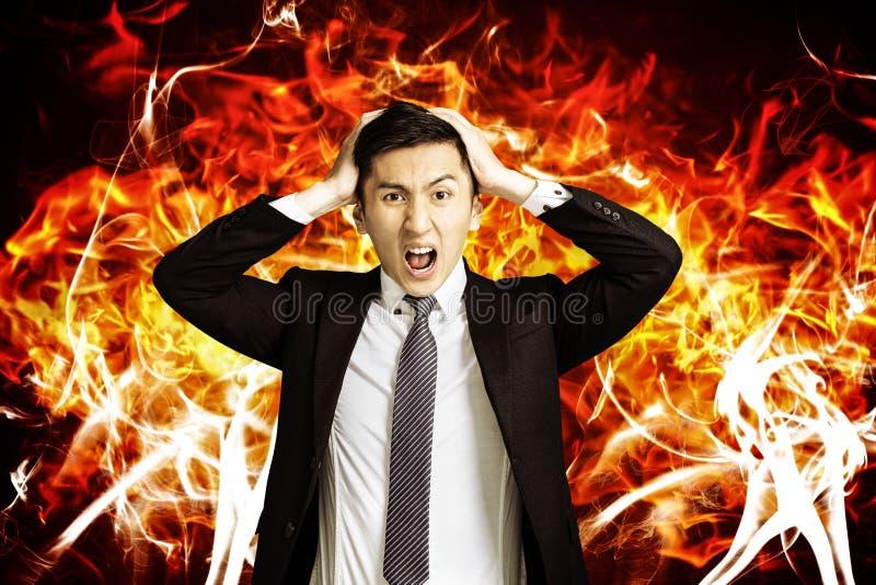 Hombre de negocios joven enojado con el fondo ardiente del fuego imagenes de archivo
