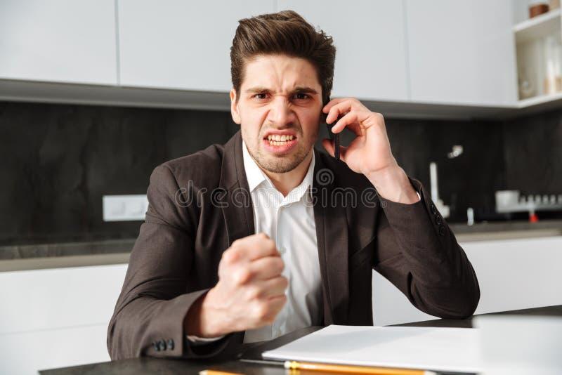 Hombre de negocios joven enojado que habla por el teléfono móvil foto de archivo