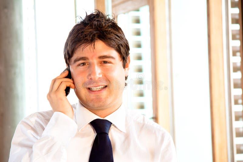 Hombre de negocios joven feliz con el teléfono celular imagenes de archivo