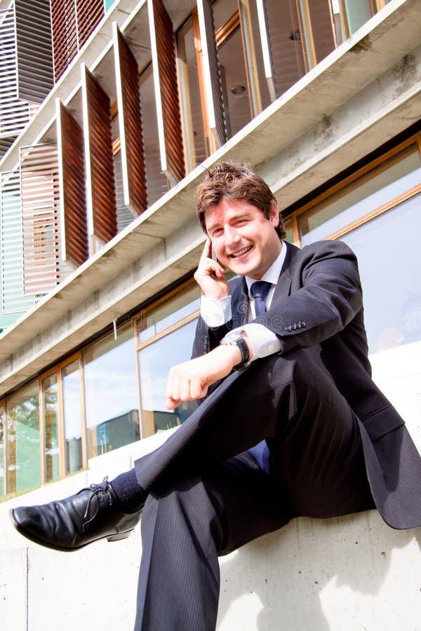 Hombre de negocios joven feliz con el teléfono celular foto de archivo