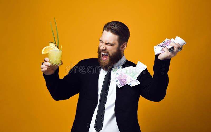 Hombre de negocios joven feliz con el vidrio del c?ctel en la ropa formal que sostiene el manojo de billetes de banco del dinero foto de archivo