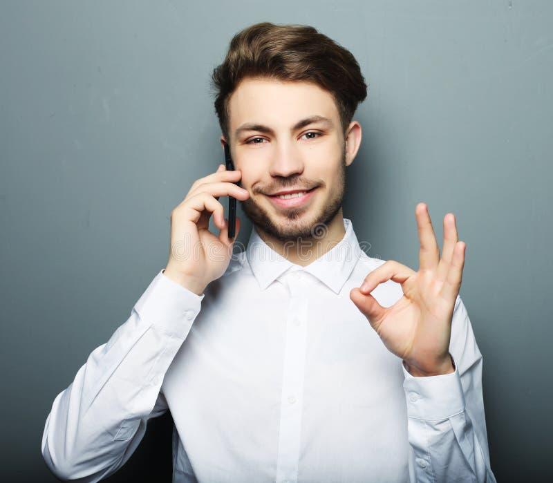 Hombre de negocios joven feliz en camisa que gesticula y que sonríe mientras que t fotografía de archivo libre de regalías