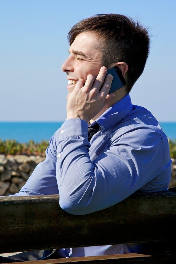 Hombre de negocios joven feliz en el teléfono que sonríe delante del océano imagenes de archivo