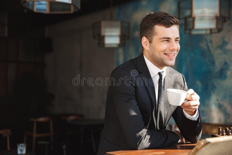 Hombre de negocios joven feliz hermoso que se sienta en café de consumición del café imagen de archivo libre de regalías