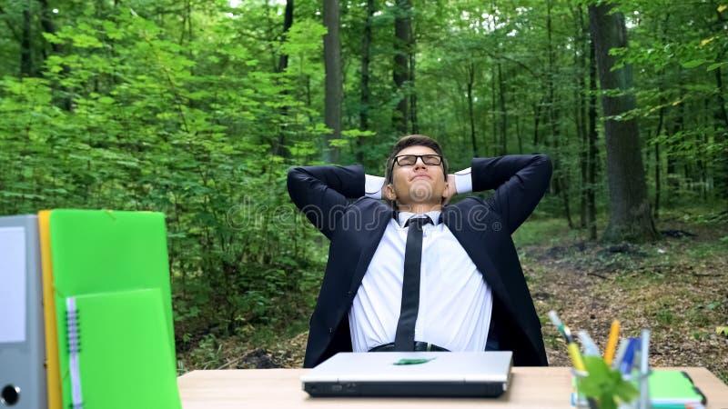 Hombre de negocios joven feliz que acaba su trabajo y que se relaja en silla en bosque verde foto de archivo