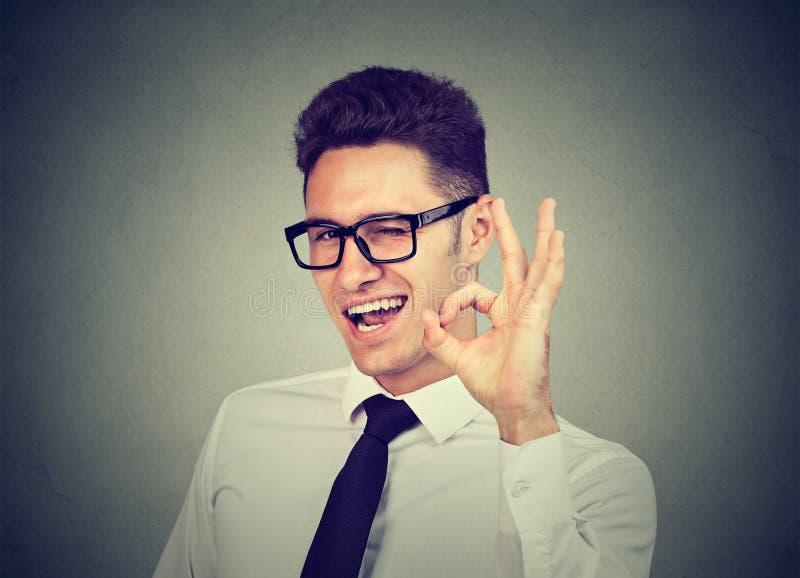 Hombre de negocios joven feliz que guiña y que muestra la muestra aceptable imagenes de archivo