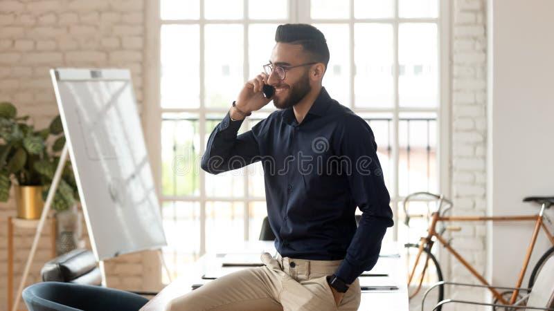 Hombre de negocios joven feliz que habla en el teléfono en sitio de la oficina foto de archivo