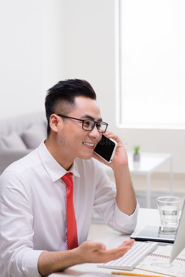 Hombre de negocios joven feliz que habla en el tel?fono celular y que usa el ordenador en oficina fotografía de archivo libre de regalías