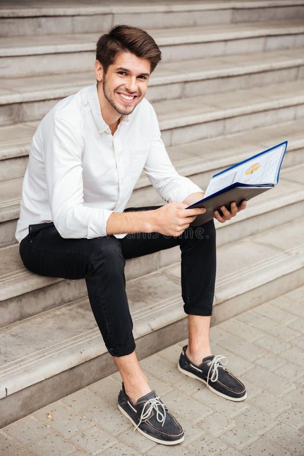 Hombre de negocios joven feliz que se sienta y que mira a través de documentos en carpeta fotografía de archivo