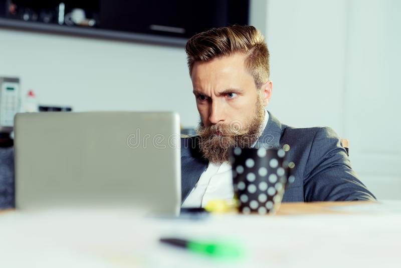 Hombre de negocios joven feliz que trabaja con el ordenador portátil en la oficina foto de archivo