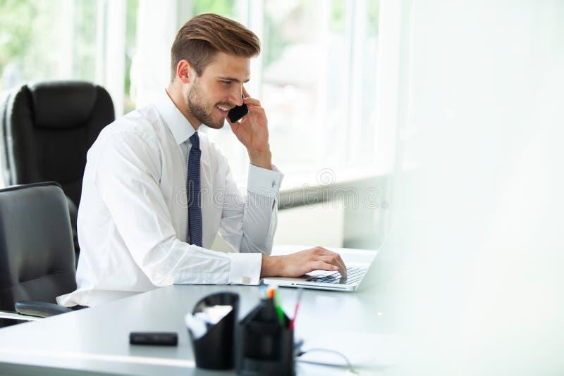 Hombre de negocios joven feliz usando el ordenador portátil en su escritorio de oficina imágenes de archivo libres de regalías