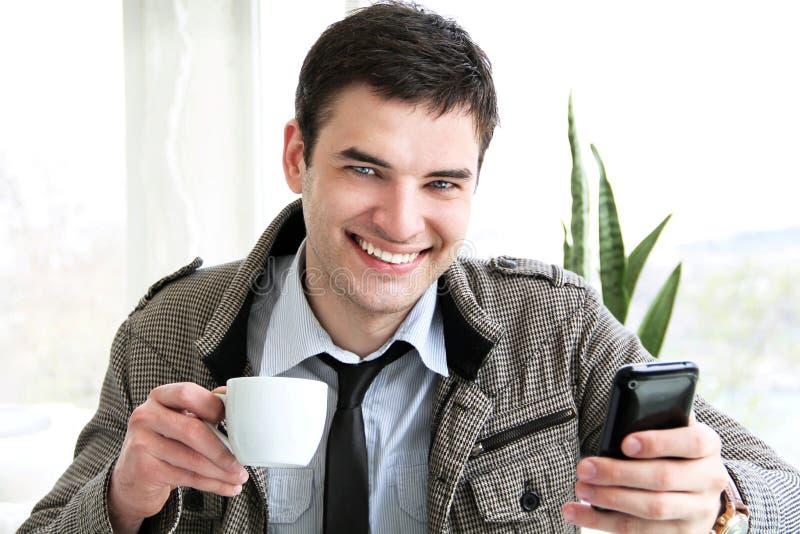 Hombre de negocios joven feliz usando el teléfono móvil fotografía de archivo libre de regalías