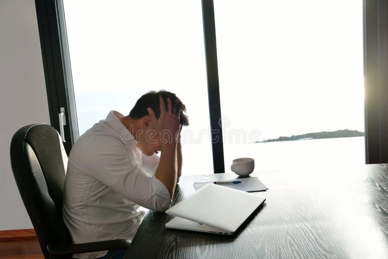 Hombre de negocios joven frustrado que trabaja en el ordenador portátil en casa imagenes de archivo