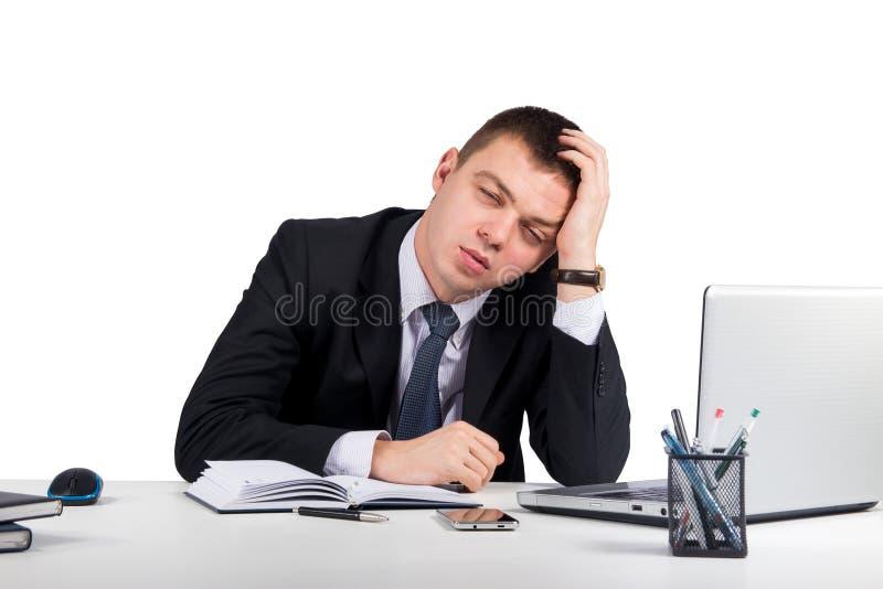 Hombre de negocios joven frustrado que trabaja en el ordenador portátil en la oficina aislada en el fondo blanco foto de archivo libre de regalías