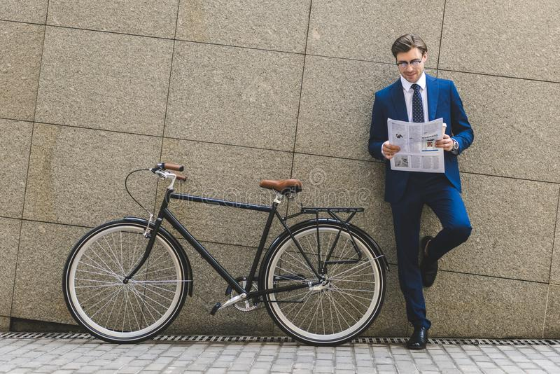 hombre de negocios joven hermoso en traje elegante con inclinarse del periódico de la lectura de la bicicleta fotografía de archivo