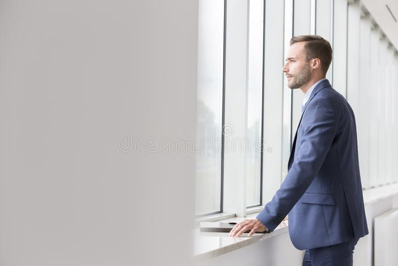 Hombre de negocios joven hermoso pensativo que mira a través de ventana en nueva oficina fotos de archivo libres de regalías