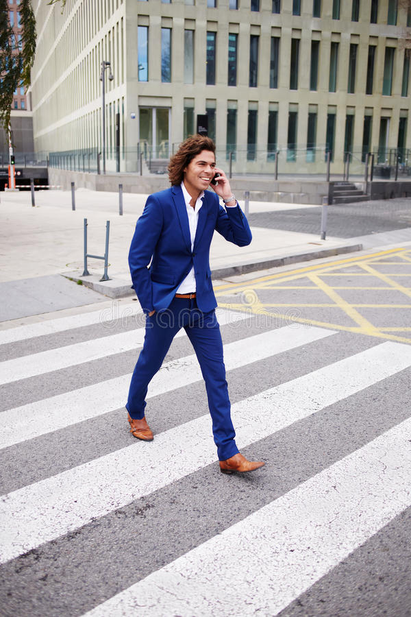 Hombre de negocios joven hermoso que habla en el teléfono en la manera con la oficina fotografía de archivo