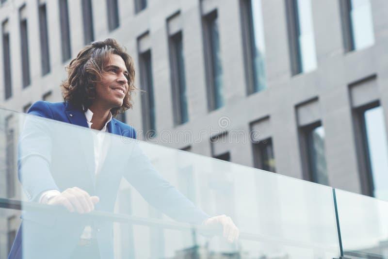 Hombre de negocios joven hermoso que se coloca en la ciudad que parece feliz y satisfecha foto de archivo