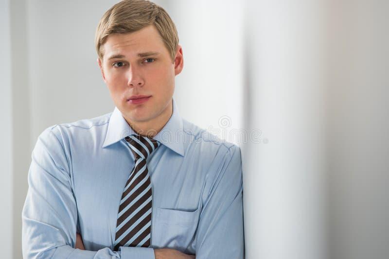 Hombre de negocios joven hermoso que se inclina contra la pared imagen de archivo