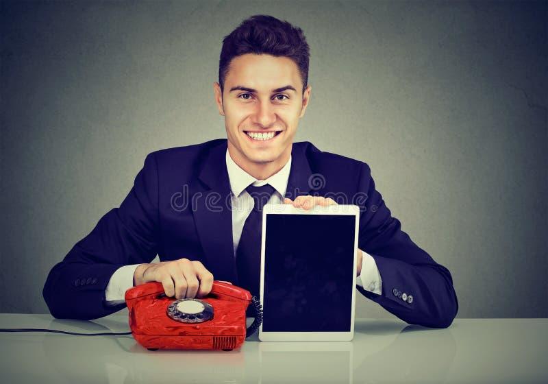 Hombre de negocios joven hermoso que se sienta en el escritorio con el teléfono y la tableta fotografía de archivo