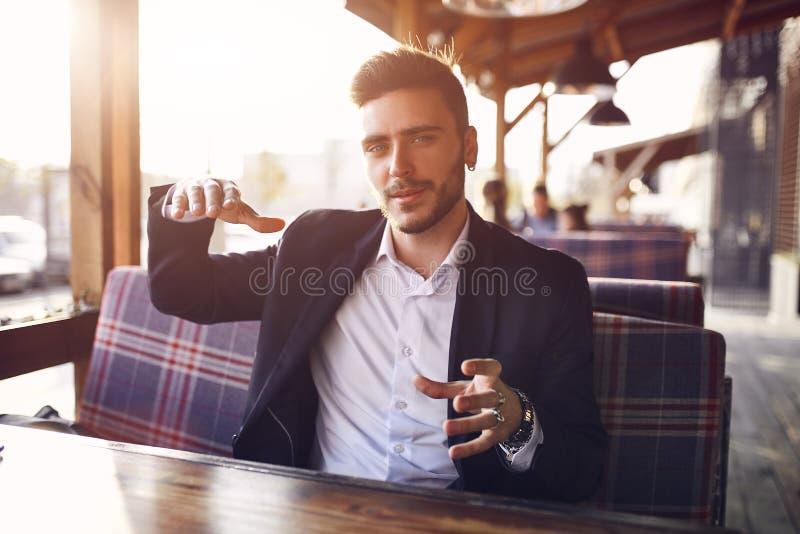 Hombre de negocios joven hermoso que se sienta en un café al aire libre del verano en el fondo de la puesta del sol de igualación fotos de archivo libres de regalías