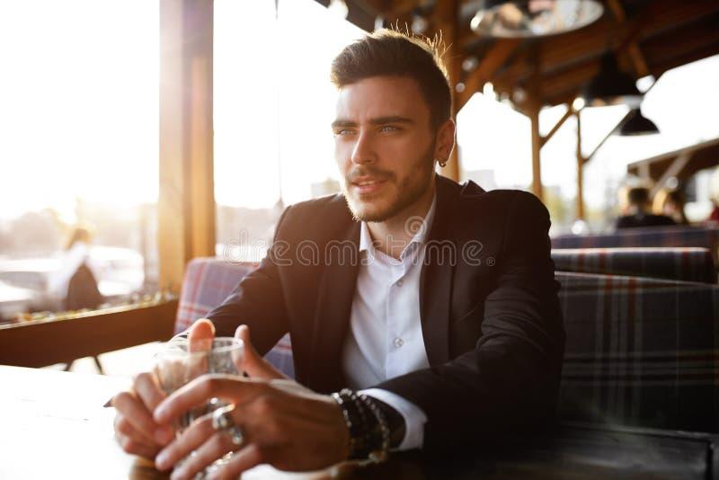 Hombre de negocios joven hermoso que se sienta en un café al aire libre del verano en el fondo de la puesta del sol de igualación foto de archivo