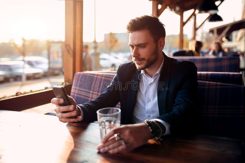 Hombre de negocios joven hermoso que se sienta en un caf? al aire libre del verano en el fondo de la puesta del sol de igualaci?n foto de archivo