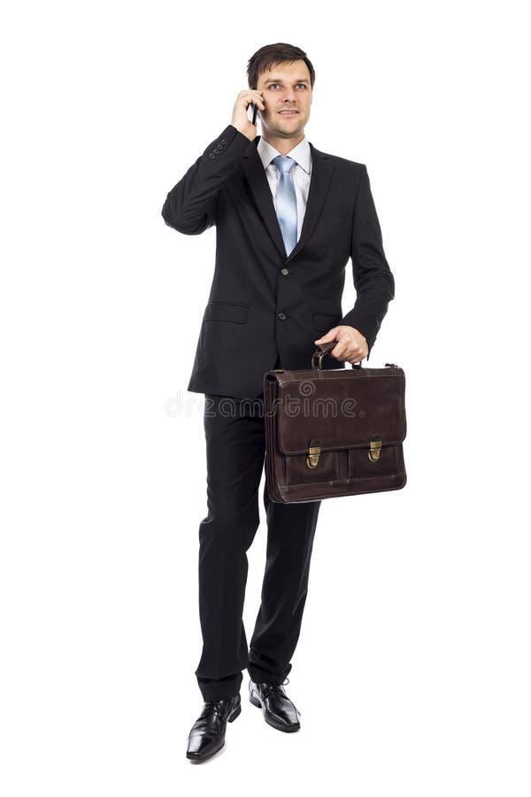 Hombre de negocios joven hermoso que sostiene una maleta fotografía de archivo