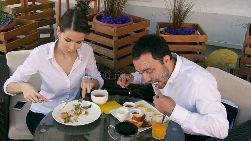 Hombre de negocios joven hermoso que tiene comida con el socio en restaurante foto de archivo libre de regalías