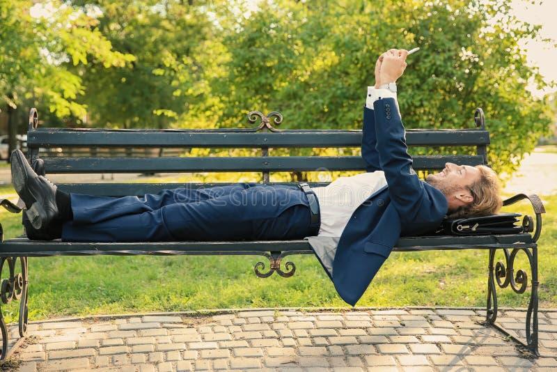 Hombre de negocios joven hermoso que toma el selfie mientras que miente en banco en parque fotos de archivo libres de regalías
