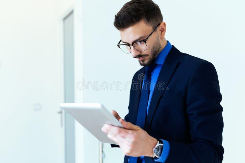 Hombre de negocios joven hermoso que trabaja con la tableta digital en la oficina imagenes de archivo